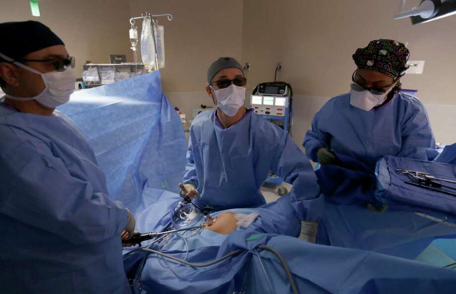 Dr. Core La, center, with Hernan Roa, left, a surgical assistant, and Lasheka LaFedge, a surgical technician, performs a 3-D laparoscopic surgery wearing special glasses at West Houston Medical Center. Photo: Melissa Phillip, Staff / © 2016 Houston Chronicle