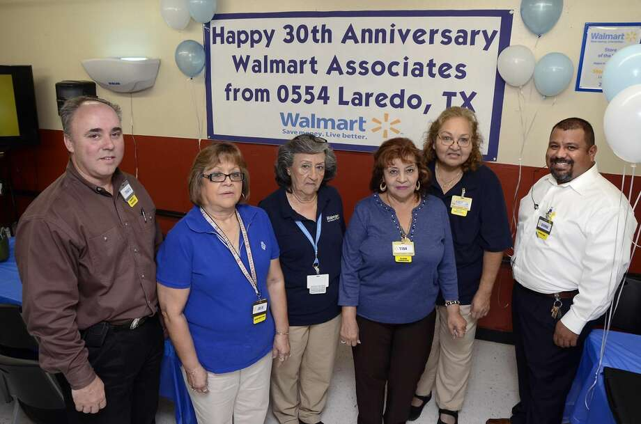 Wal-Mart Market Manager Travis Bailey, left and Wal-Mart Store 0554 manager George Herrera, right pose Wednesday morning with Julie Fraga, Ofelia Palacios, Tina Lopez and Mary Lou Bejarano who are celebrating their 30th Anniversary with Wal-Mart. (Photo by: Cuate Santos