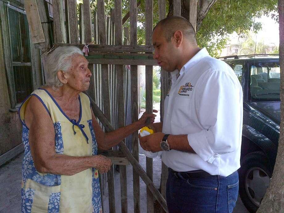 Everardo Quiroz Torres, candidato del PRD a Presidente Municipal de Nuevo Laredo, México, saluda a una mujer residente en la Colonia Infonavit Fundadores. (Foto de cortesía)