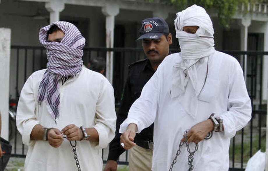 FILE - In this Friday, Sept. 23, 2016 file photo, a Pakistani police officer escorts father Mohammad Shahid, right, and ex-husband Mohammad Shakeel of slain British-Pakistani woman Samia Shahid to a court in Jhelum, Pakistan. A defense lawyer says Tuesday, Sept. 27, 2016 that Pakistani court has opened the trial against the father and ex-husband of a British woman over her alleged rape and murder in the name of so-called honor. (AP Photo/Anjum Naveed, File)