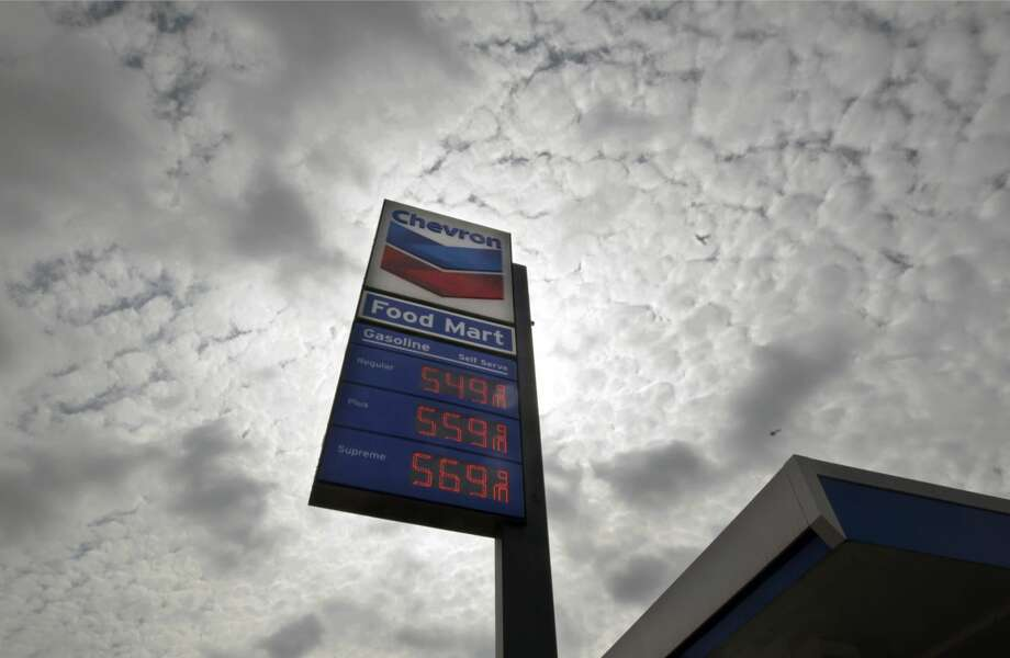 "In this Tuesday, Oct. 9, 2012, file photo, a Chevron station posts gasoline prices starting at $5.50 per gallon in downtown Los Angeles. Shares of Chevron Corp. plunged Wednesday after the oil giant said its third-quarter earnings are expected to be ""substantially lower"" than in the second quarter. (AP Photo/Reed Saxon, File)"