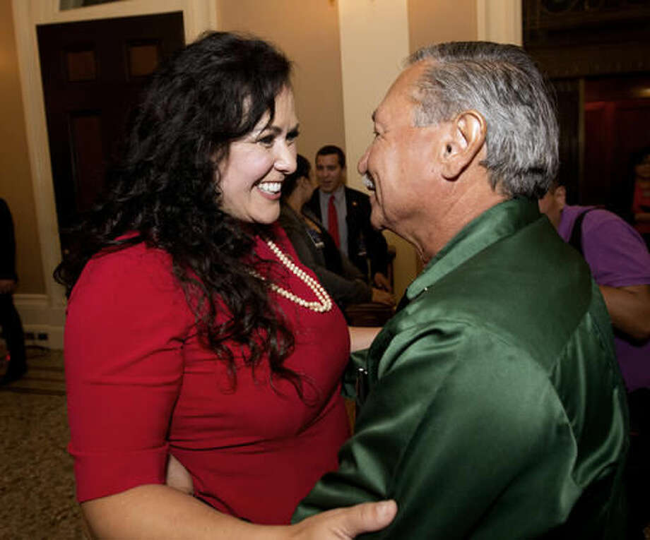 Assemblywoman Lorena Gonzalez, D-San Diego, receives congratulations from Arturo Rodriguez, president of the United Farm Workers, after the Assembly approved her bill requiring farmworkers to receive overtime pay after working eight hours, at the Capitol, in Sacramento, Calif. Calif. Gov. Jerry Brown, announced that he signed Gonzalez' bill, AB1066, Monday, Sept. 12, 2016. (AP Photo/Rich Pedroncelli,file)
