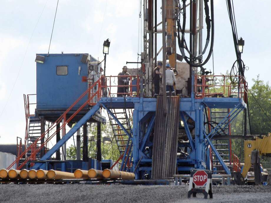 In this June 25, 2012 file photo, a crew works on a gas drilling rig at a well site for shale based natural gas in Zelienople, Pa. (AP Photo/Keith Srakocic)