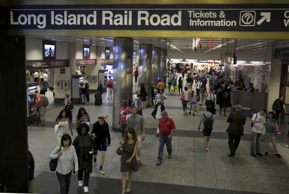 FILE - In this July 16, 2014 file photo, passengers walk through the Long Island Rail area of New York's Penn Station. Plans are in place for the long-awaited renovation of the country's busiest rail station. They include widening concourses, raising ceilings and creating a sparkling, light-filled waiting area across the street from the dreary facility below New York's Madison Square Garden. (AP Photo/Richard Drew, File)