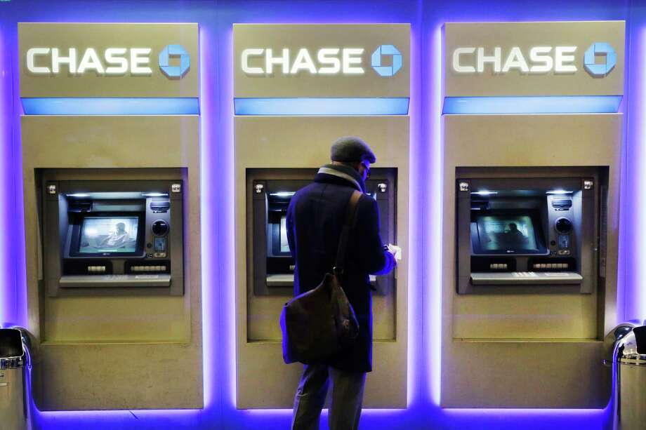 FILE - In this Wednesday, Jan. 14, 2015, file photo, a customer uses an ATM at a branch of Chase Bank, in New York. Fewer Americans are without access to a checking or savings account, according to a survey released Thursday, Oct. 20, 2016, by federal regulators, a sign that the improving economy is helping lift the nation's poorest households. (AP Photo/Mark Lennihan, File) Photo: Mark Lennihan, STF / Copyright 2016 The Associated Press. All rights reserved. This material may not be published, broadcast, rewritten or redistribu