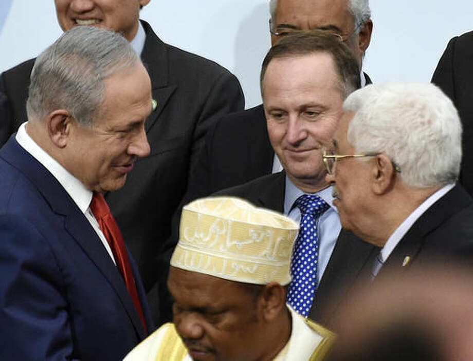 "FILE -- In this Nov. 30, 2015 file photo, Israeli Prime Minister Benjamin Netanyahu, left, talks with Palestinian President Mahmoud Abbas, right, at the COP21, the United Nations Climate Change Conference, in Le Bourget, outside Paris, . Russia's Foreign Ministry says Israeli and Palestinian leaders have agreed ""in principle"" to meet in Moscow for talks. The ministry's spokeswoman Maria Zakharova said on Thursday, Sept. 8, 2016, that Moscow has heard from the offices of Abbas and Netanyahu that he two are confirming they agreed to meet in Moscow, though it's not clear when that will happen. No date has been set. (Martin Bureau/Pool Photo via AP, File)"
