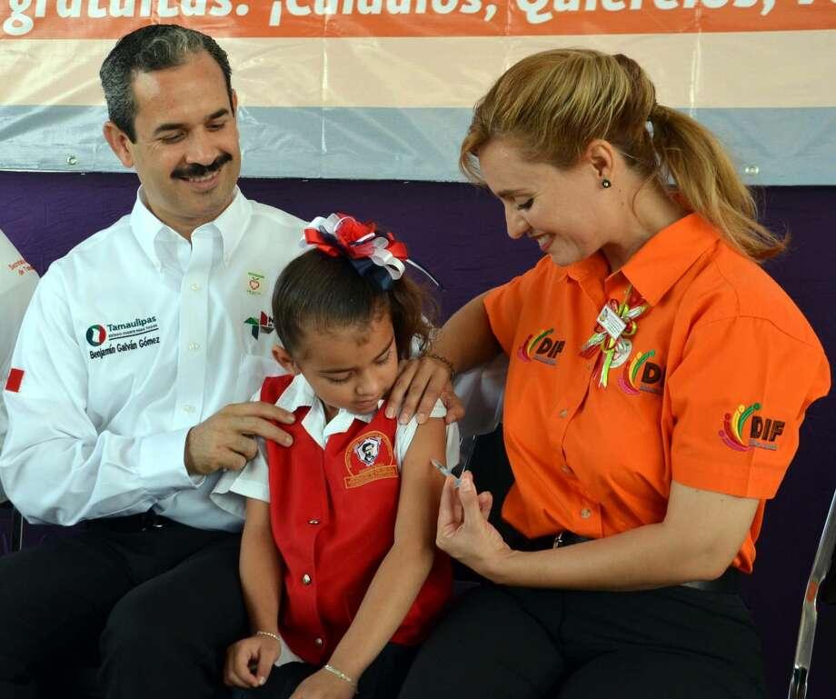 La Presidenta del Sistema DIF Nuevo Laredo, Martha Alicia Aldapa, aplica una vacuna en el marco del arranque de la Semana Nacional de Salud. Observa a la izquierda el Presidente Municipal, Benjamín Galván.