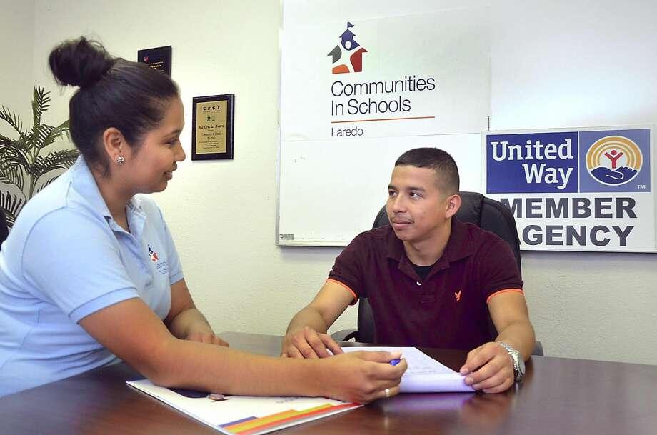 Gladys Salinas, coordinadora del programa Comunidades en las Escuelas (Communities in Schools), platica con el ex estudiante en CIS, Alexis Vásquez, en la oficina de la organización. (Foto por Cuate Santos)