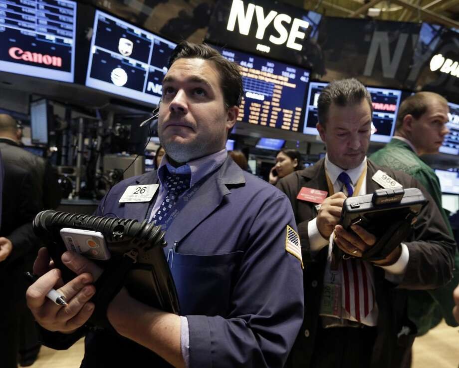 Joseph Lawler, left, works with fellow traders on the floor of the New York Stock Exchange, Friday, Oct. 18, 2013. Stronger economic growth in China and a pickup in U.S. corporate earnings are sending the stock market mostly higher in early trading. (AP Photo/Richard Drew)
