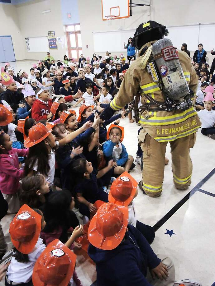 Laredo Fire Fighter Fernando Fernandez Jr., wears his mask and suit along with a fire tank as he shakes hands with students at Killam Elementary Tuesday morning. Fire department personnel have been visiting elementary schools throughout October to offer safety tips in observance of National Fire Prevention Month. (Photo by: Cuate Santos