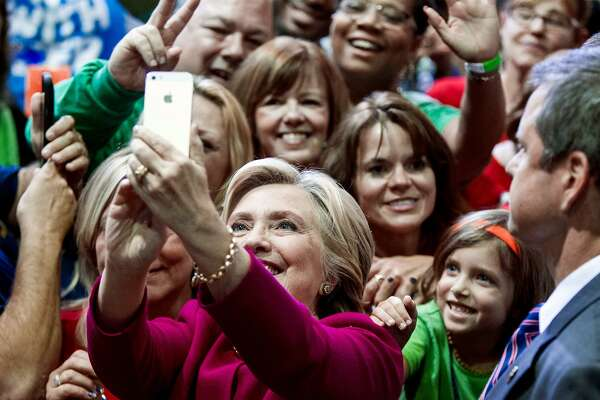 Democratic presidential candidate Hillary Clinton takes a selfie with supporters at a campaign rally at the Zembo Shrine in Harrisburg, Pa. on Oct. 4.