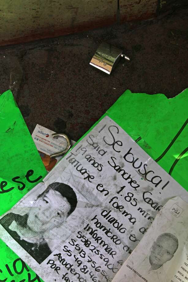 "A broken padlock and signs with the details of people that were recently abducted lie on the sidewalk in front of an after hours bar in Mexico City, Friday May 31, 2013. Anguished relatives said that on Sunday May 26, eleven young people were kidnapped in broad daylight from an after-hours bar in Mexico City's Zona Rosa, a normally calm district of offices, restaurants, drinking spots and dance clubs. Sign says: ""Looking for Said Sanchez Garcia, 19 years old, height 1.85 mts., tattoo in the shape of a devil on his right shoulder."" (AP Photo/Marco Ugarte)"