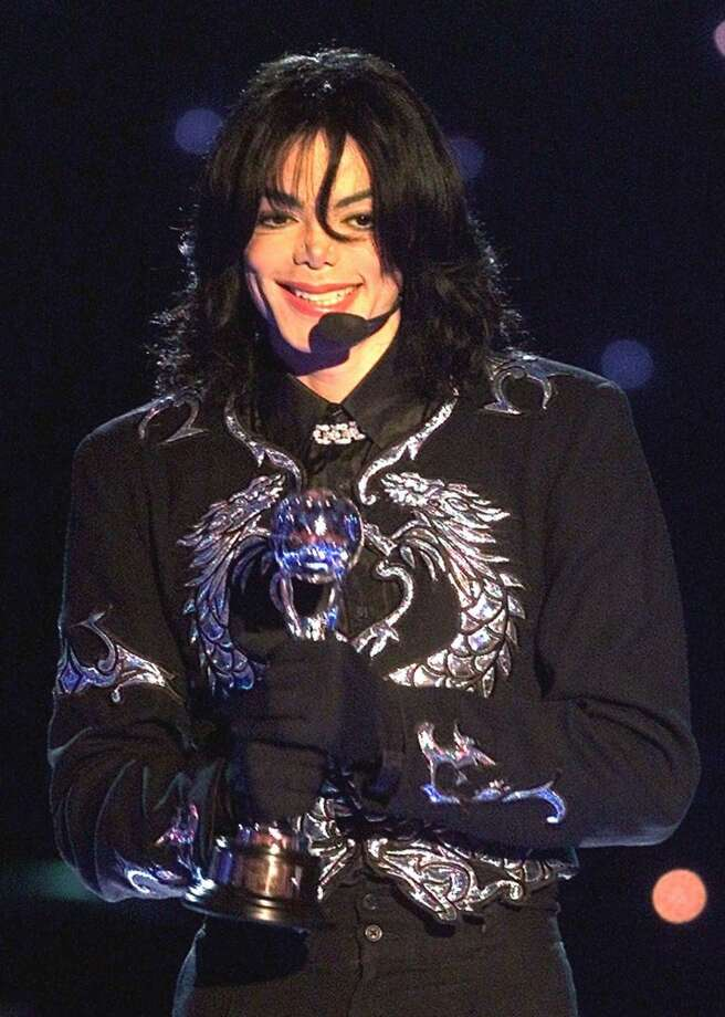 "FILE - In this May 10, 2000 file photo, pop star Michael Jackson gestures to spectators as he holds the ""Millennium Award"" which was awarded to him at the 2000 World Music Awards ceremony in Monaco. A Los Angeles jury on Wednesday Oct. 2, 2013, rejected a negligence lawsuit by Jackson's mother, Katherine Jackson, against AEG Live LLC that claimed the concert promoter was responsible for hiring the doctor convicted of causing her son's 2009 death. (AP Photo/Lionel Cironneau, file)"