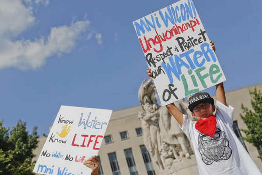 Tusweca Mendoza, 10, of Arlington, Va., originally from Pine Ridge, S.D., holds up a sign outside U.S. District Court in Washington, Tuesday, Sept. 6, 2016, as members of the Standing Rock Sioux Tribe have asked a federal judge to temporarily stop work on parts of the Dakota Access Pipeline to prevent the destruction of sacred and culturally significant sites near Lake Oahe. (AP Photo/Pablo Martinez Monsivais)