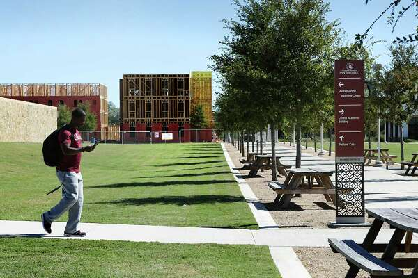 A Texas A&M San Antonio student walks to a class, passing the residential halls under construction.  Friday, Oct. 21, 2016.