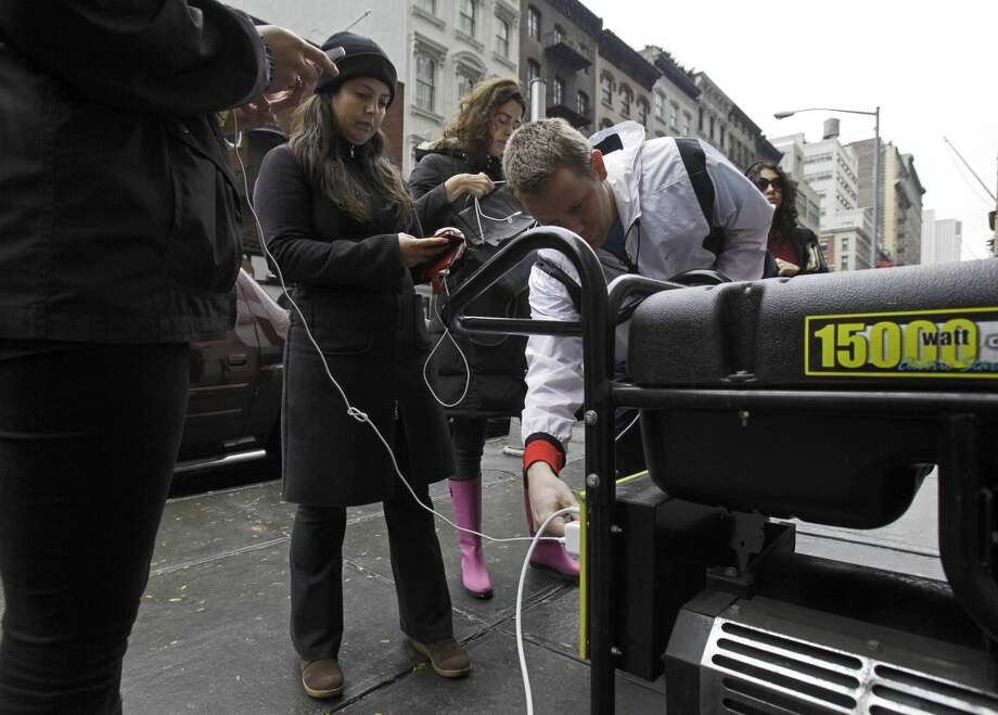 People in New York's Tribeca neighborhood, without power because of superstorm Sandy, wait for a chance to charge their mobile phones on an available generator setup on a sidewalk, Tuesday, Oct. 30, 2012. Sandy, the storm that made landfall Monday, caused multiple fatalities, halted mass transit and cut power to more than 6 million homes and businesses. (AP Photo/Richard Drew)
