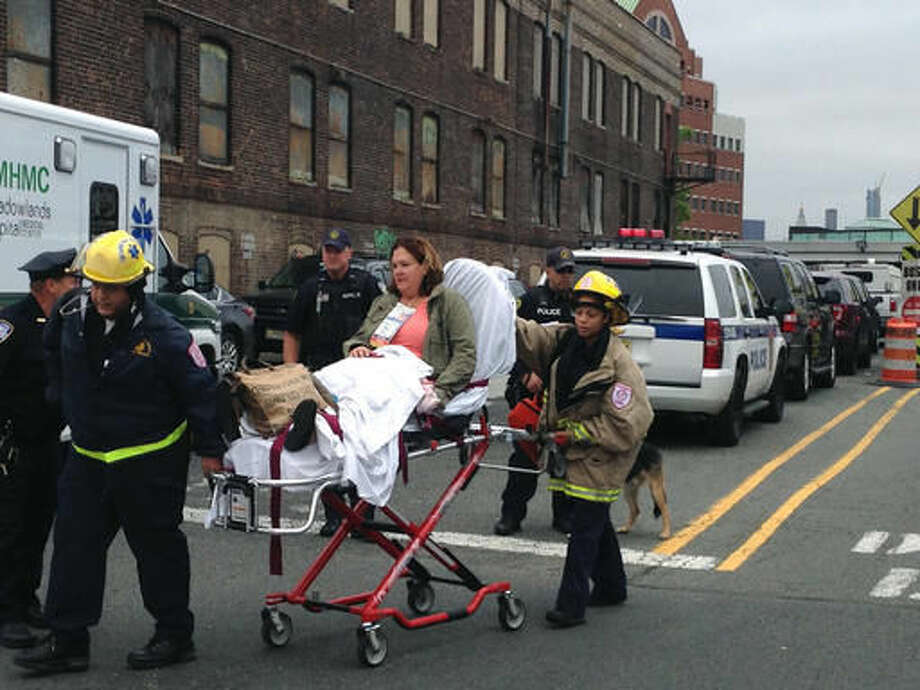 A woman is wheeled away from the Hoboken Terminal train station on a stretcher Thursday Sept. 29, 2016, after a New Jersey Transit commuter train from New York barreled into the station during the morning rush hour, in Hoboken, N.J. (AP Photo/Karen Matthews)