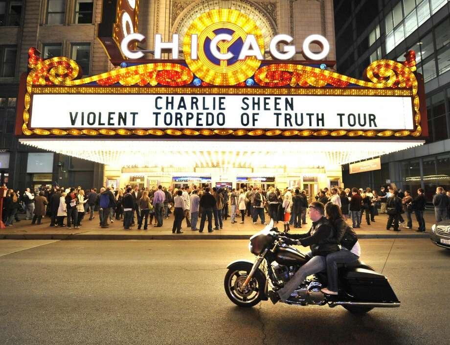A motorcycle drives by the Chicago Theatre before Charlie Sheen's performance, Sunday, April 3, in Chicago. Promising 'the real story,' the 45-year-old former 'Two and a Half Men' star continued his month-long, 20-city variety show tour, with Sunday's sold-out show in Chicago. (Photo by Brian Kersey