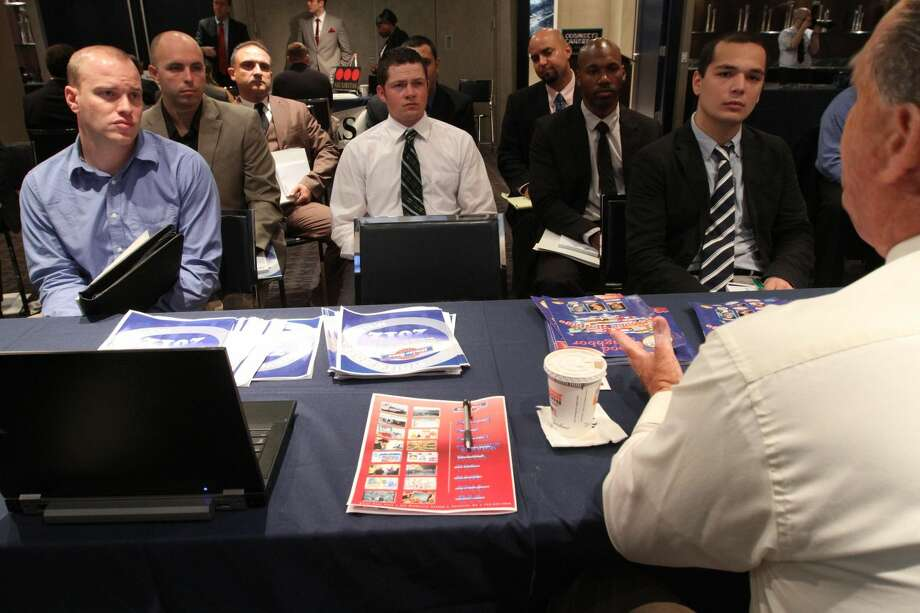 In this Friday Sept. 28, 2012, photo, a group of veterans listen as a representative from White Rose Foods, foreground right, talks about their agency during a job fair introducing veterans to careers in the security and private investigations industry at Yankee Stadium in the Bronx borough of New York. Weekly applications for U.S. unemployment benefits jumped 46,000 in the week ending on Thursday, Oct.18, 2012, to a seasonally adjusted 388,000, the highest in four months. The increase represents a rebound from the previous week's sharp drop. Both swings were largely due to technical factors. (AP Photo/Tina Fineberg)