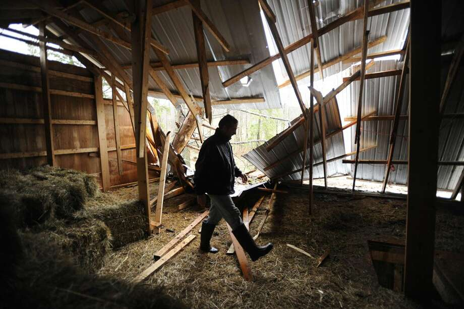 Aaron Hofelt surveys the damage after high winds from superstorm Sandy blew two trees into the barn on his property in Port Matilda, Pa., Tuesday, Oct. 30, 2012. Sandy, the storm that made landfall Monday, caused multiple fatalities, halted mass transit and cut power to more than 6 million homes and businesses. (AP Photo/Centre Daily Times, Nabil K. Mark)