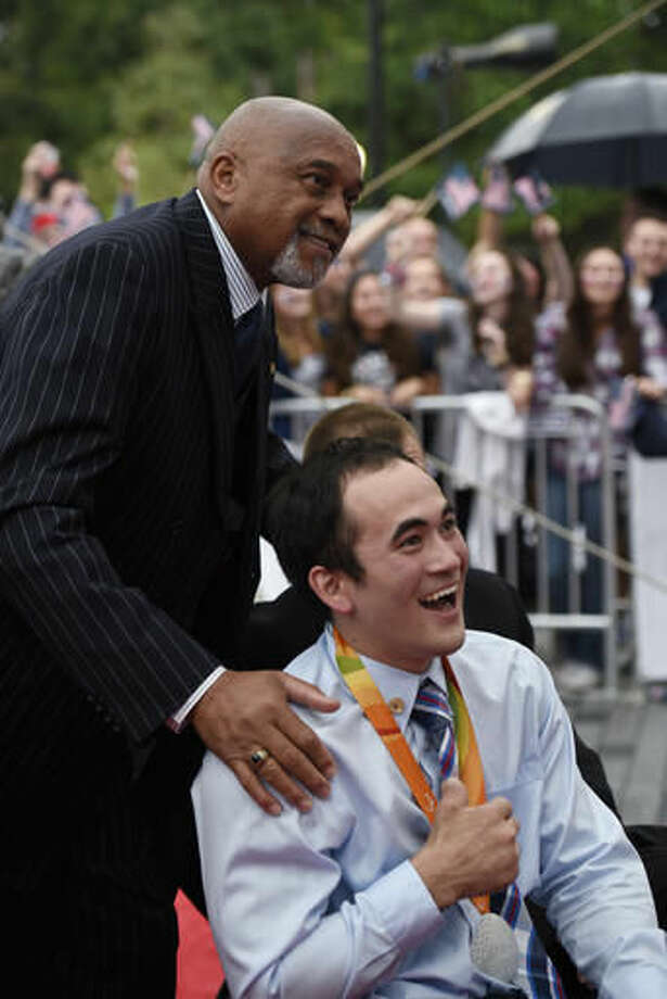 Tommie Smith, left, poses for a photograph with U.S. wheelchair rugby player Chuck Aoki in Washington on Wednesday, Sept. 28, 2016. Smith and John Carlos voiced their support for Colin Kaepernick and other athletes staging national anthem protests, 48 years after they raised their gloved fists on the podium in a symbolic protest at the Olympics. (AP Photo/Sait Serkan Gurbuz)