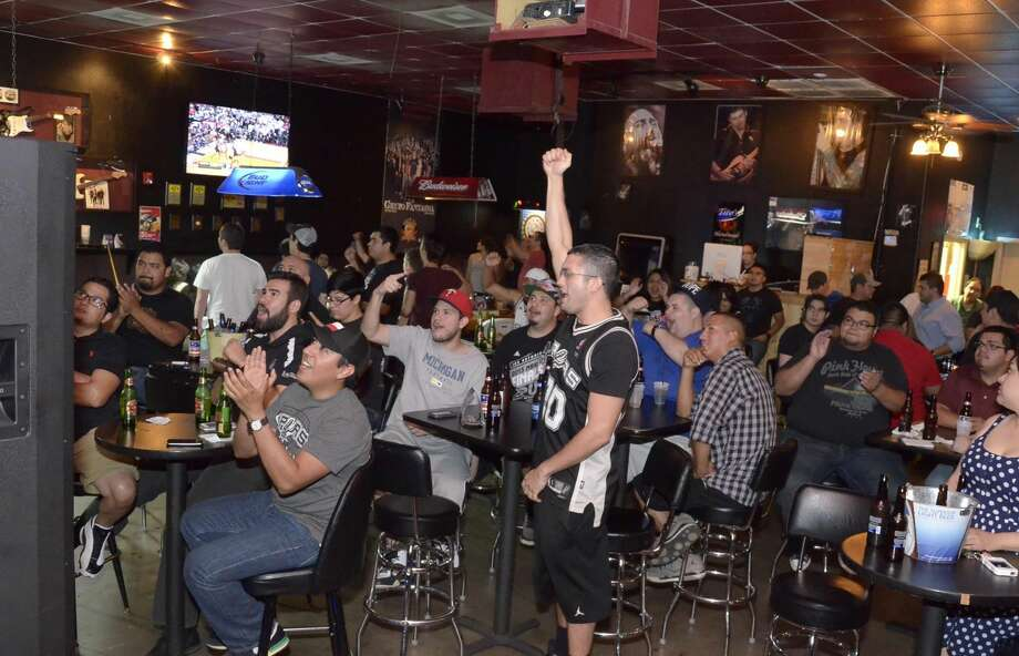 Fans cheer at Average Joe's as they watch the San Antonio Spurs play against the Miami Heat during game six of the NBA Finals on Tuesday evening. The Heat defeated the Spurs 103-100 filled with controversial calls. Game seven starts 8 p.m. Thursday night. (Danny Zaragoza/Laredo Morning Times)