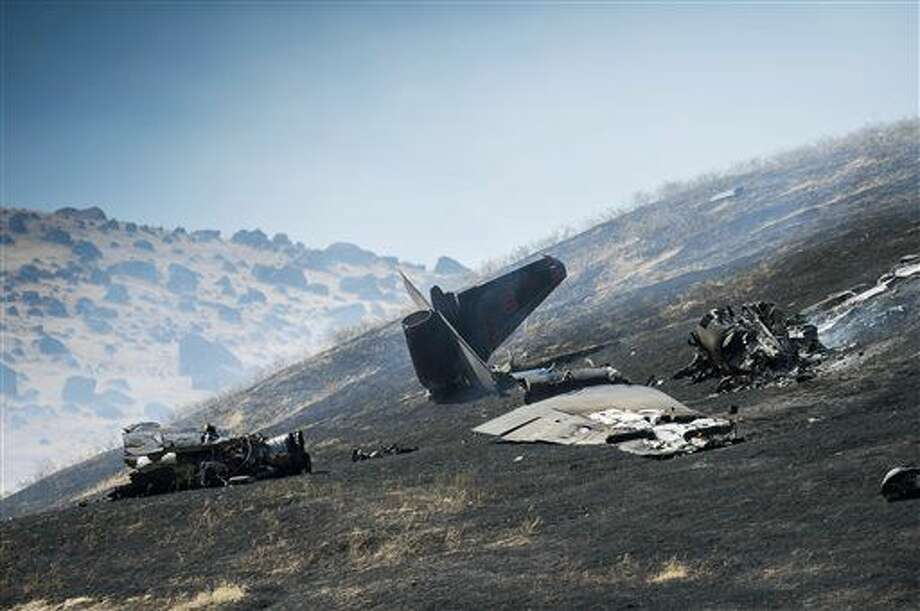 ADDS CONDITION OF PILOTS - An aircraft assigned to the 1st Reconnaissance squadron at Beale Air Force Base and on a training mission went down on the lower slopes of the Sutter Buttes on Tuesday, Sept. 20, 2016 in Sutter County, Calif. The U.S. Air Force says one pilot was killed, and one was injured after they ejected from the plane. (Hector Amezcua/The Sacramento Bee via AP)