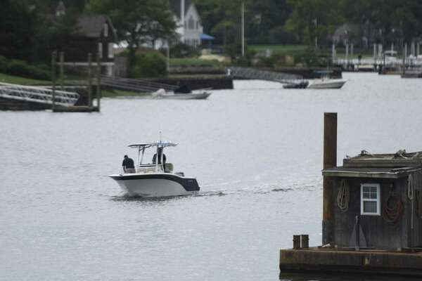 A boat returns to the Cos Cob Harbor near Cos Cob Park in Greenwich, Conn. Wednesday, June 8, 2016. Officials say a long-awaited project to dredge the harbor will begin as soon as the weather allows, possibly Monday.