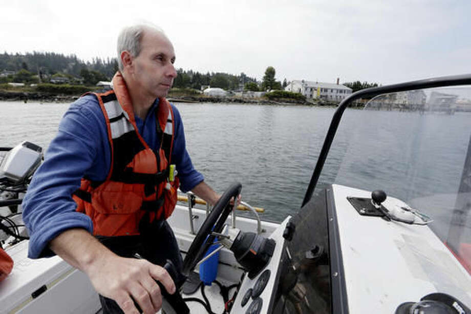 Paul McElhany, a research ecologist with NOAA's Northwest Fisheries Science Center, pilots a boat to retrieve Dungeness crab larvae from light-catching traps set out the day before in the marine waters outside of the center's station in Mukilteo, Wash., on July 26, 2016. The crabs, found from central California to the Aleutian Islands, Alaska, play an important role in the ocean's ecosystem. (AP Photo/Elaine Thompson)