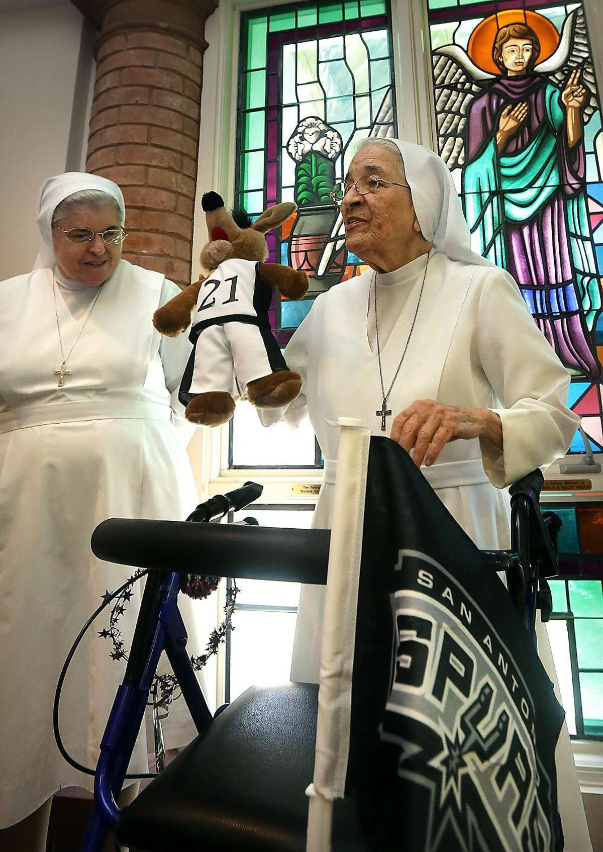 Sister Rosalba Garcia, right, holds a Coyote doll as Sister Kathy Keane looks on Wednesday, June 19 in San Antonio. Nuns from the Salesian Sisters love their Spurs and pray for them before and during games. (Photo by Bob Owen/San Antonio Express-News)