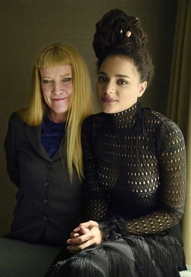 """In this Sept. 11, 2016 photo, writer-director Andrea Arnold, left, and cast member Sasha Lane, from the film, """"American Honey,"""" pose at the InterContinental Toronto Centre in Toronto. The film is a cross-country road trip of aimless but colorful youths selling magazines door-to-door as a way to party across the Midwest. (Photo by Chris Pizzello/Invision/AP)"""