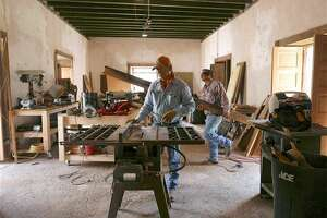 In this Wednesday, Sept. 15, 2016 photo, Jose Yzaguirre, left, and Victor Yzaguirre work with wood in a room at the Trevino-Uribe Ranch, as part of a restoration process, in San Antonio, Texas. The first structure at the site was built in 1830 in San Ygnacio, Texas. (Billy Calzada/The San Antonio Express-News via AP)