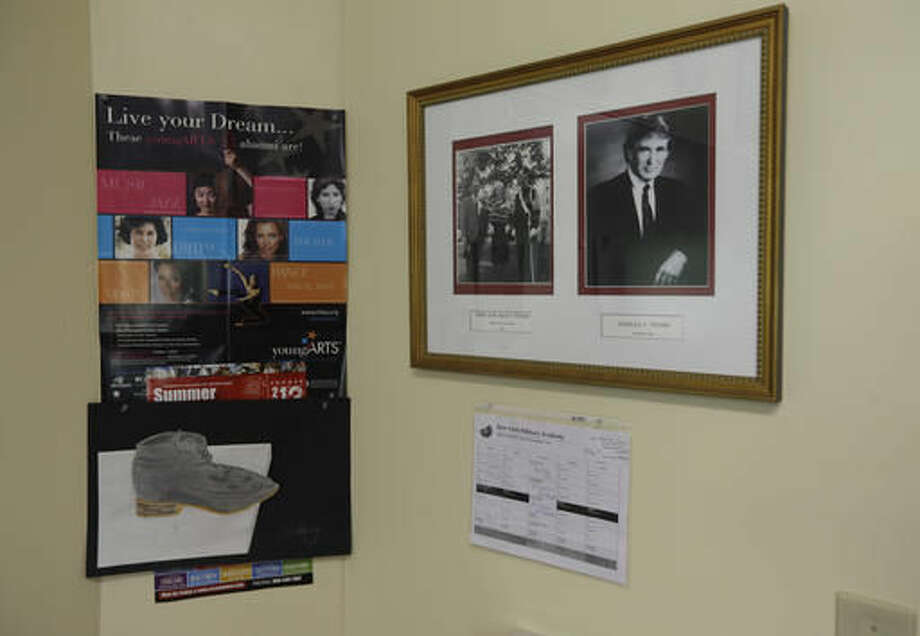 In this Thursday, Sept. 8, 2016 photo, photos of Donald Trump, right, and Trump with his parents, hang on a classroom wall at the New York Military Academy, in Cornwall-on-Hudson, N.Y. While Republican presidential nominee, Trump, talks tough about dealing with China, his old military prep school is building bridges to that country. The New York Military Academy began classes this fall with new Chinese backing and a former New York City high school principal originally from China in charge. (AP Photo/Mike Groll)