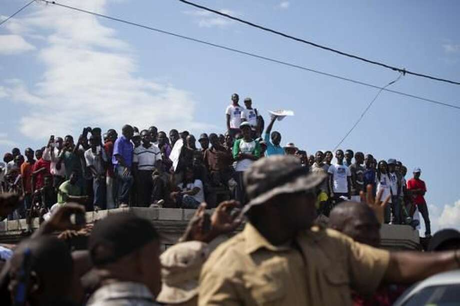 In this Sept. 21, 2016 photo, supporters of Haiti's former President Jean Bertrand-Aristide stand on top of a roof to listen to him speak during a campaign event for presidential candidate Maryse Narcisse in Port-au-Prince, Haiti. Aristide's return to open campaigning for an ally is energizing supporters in poor neighborhoods who see the former slum priest as a near-messianic figure who fights for the country's most marginalized. Haiti will hold elections on Oct. 9. (AP Photo/Dieu Nalio Chery)
