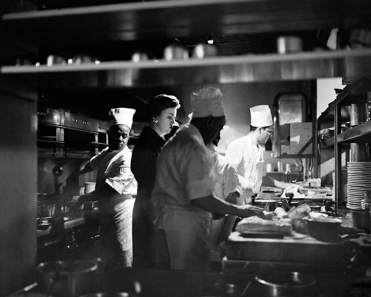 Ella Brennan with her chef Paul Blange (to the right of Brennan) in the kitchen of the Vieux Carre Restaurant in the French Quarter of New Orleans. From the documentary