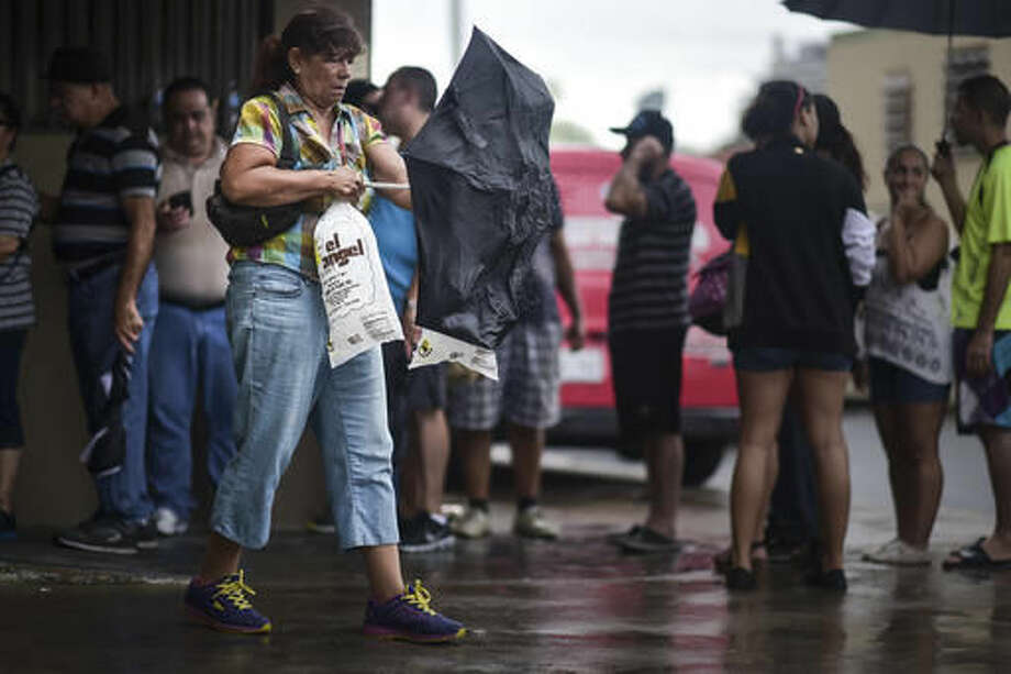 A woman carries a bag of ice that she bought at El Angel Ice Plant during a massive blackout in San Juan, Puerto Rico, Thursday, Sept. 22, 2016. Puerto Ricans faced another night of darkness Thursday as crews slowly restored electricity a day after a fire at a power plant caused the aging utility grid to fail and blacked out the entire island. (AP Photo/Carlos Giusti)