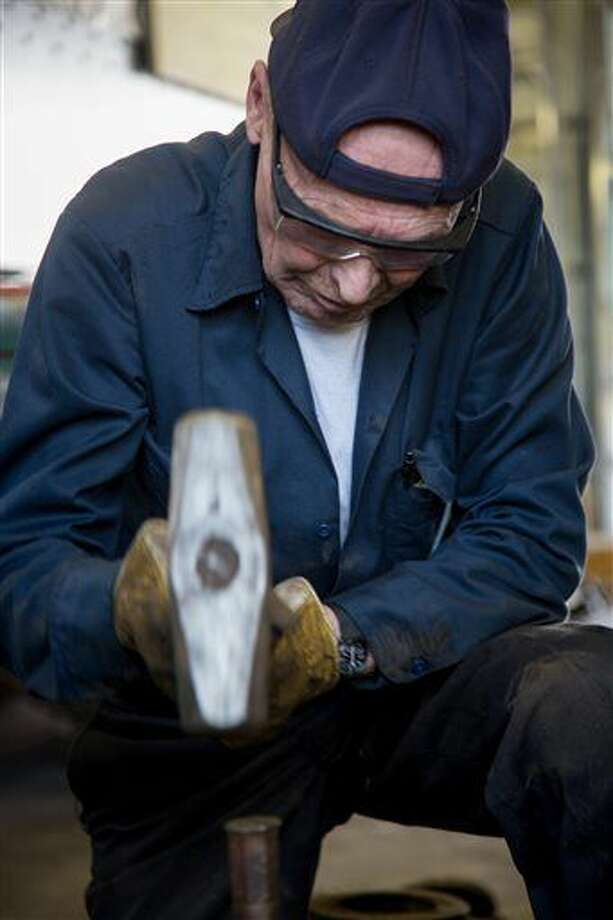 In this Saturday, Sept. 3, 2016 photo, John Barrett tries to loosen up a stuck pin in the drive rods of Engine 223, in Ogden, Utah. After several different attempts with wrenches and a hydraulic press, the pin was eventually loosened with a combination of heat, grease and lots of hammering. (Benjamin Zack/Standard-Examiner)