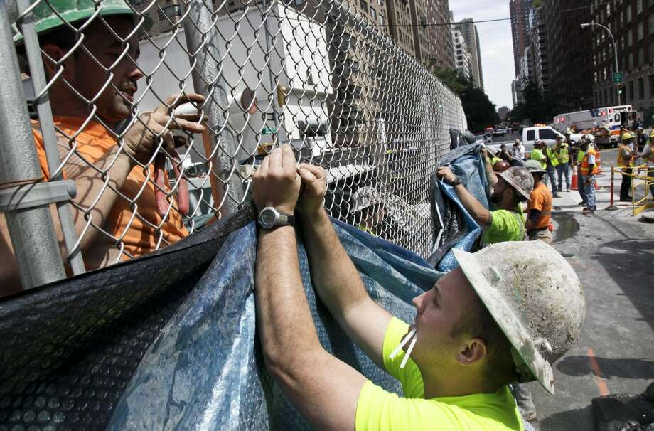In this Aug. 21, 2012, photo, construction workers hang tarp to block the view of damage following an intentional underground explosion on the Second Avenue subway project on East 72nd. (AP Photo/Bebeto Matthews)