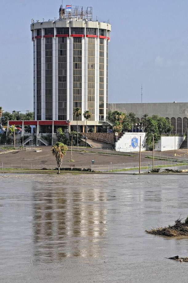 The reflection of the Rio Grande Plaza Hotel can be seen in the water as the Rio Grande floods the Dos Laredos Park and El Portal parking lots Monday morning. (Photo by Ulysses S. Romero/Laredo Morning Times)