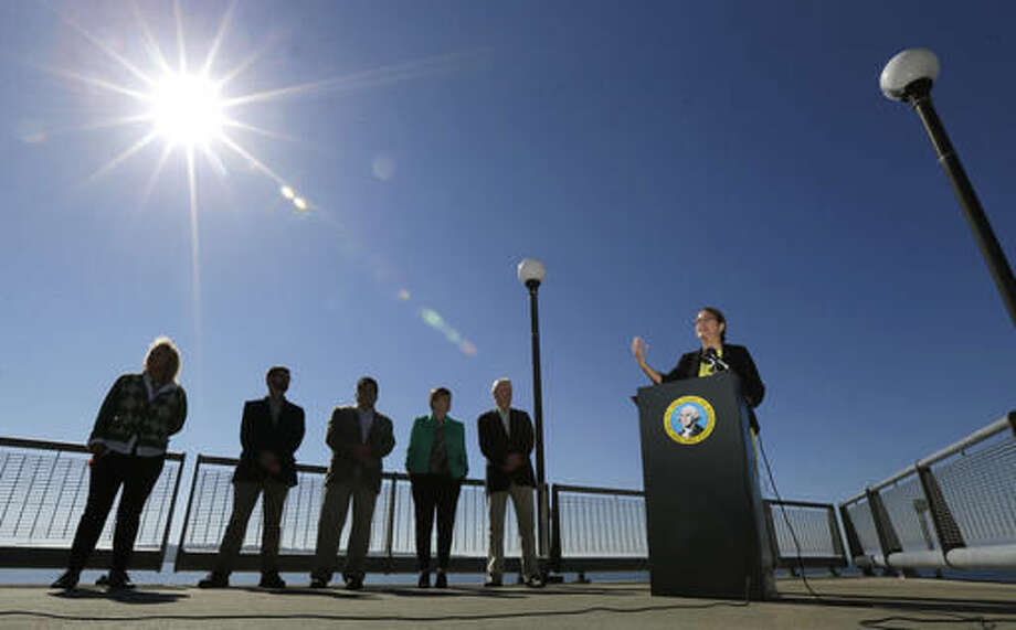 Maia Bellon, right, director of the Washington State Dept. of Ecology, speaks at a press conference, Thursday, Sept. 15, 2016, overlooking Elliott Bay in Seattle. Washington state environmental regulators finalized a new rule Thursday to limit greenhouse gas emissions from large polluters. (AP Photo/Ted S. Warren)