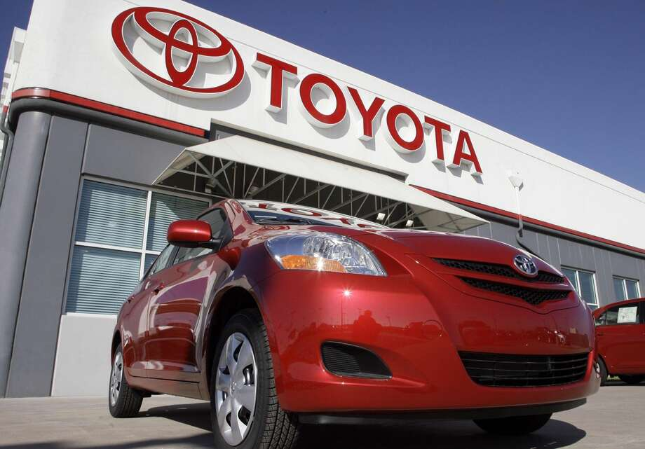 In this Oct. 22, 2006 file photo, the Toyota sign hangs over a 2007 Yaris sedan on sale on the lot of a Toyota dealership in the southeast Denver suburb of Centennial, Colo. Toyota Motor Corp. is recalling 7.43 million vehicles in the U.S., Japan, Europe and elsewhere around the world for a faulty power-window switch — the latest, massive quality woes for Japan's top automaker. The recall, announced Wednesday, Oct. 10, 2012 affects more than a dozen models produced from 2005 through 2010. (AP Photo/David Zalubowski, File)