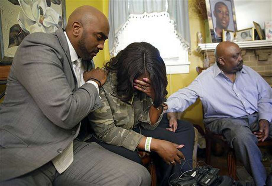 Attorney Damario Solomon-Simmons, left, comforts Tiffany Crutcher, twin sister of Terence Crutcher who was shot and killed by Tulsa Police Friday night Sept. 16, 2016. At right is Rev. Joey Crutcher, her and Terence's father. (Mike Simons/Tulsa World via AP)