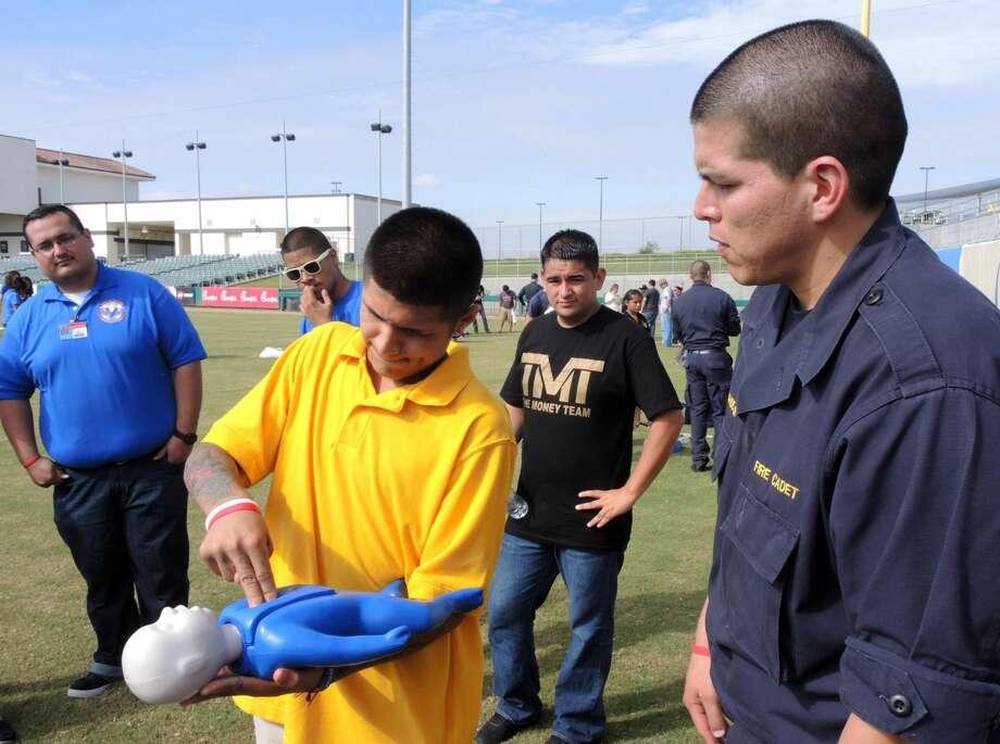 Un estudiante de Jose A. Valdez High School, Jorge Torres, al momento de estar recibiendo instrucciones sobre como aplicar CPR a un infante, por el cadete del Departamento de Bomberos de Laredo Jesus Hernandez el viernes en el Estadio Uni-Trade. Foto por cuate Santos