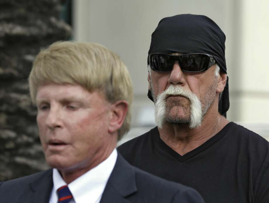 "Reality TV star and former pro wrestler Hulk Hogan, whose real name is Terry Bollea, looks on as his attorney David Houston speaks during a news conference Monday, Oct. 15, 2012 at the United States Courthouse in Tampa, Fla. Hogan says he was secretly taped six years ago having sex with the ex-wife of DJ Bubba ""The Love Sponge"" Clem. Portions of the video of Hogan and Heather Clem were posted on the online gossip site Gawker. (AP Photo/Chris O'Meara)"
