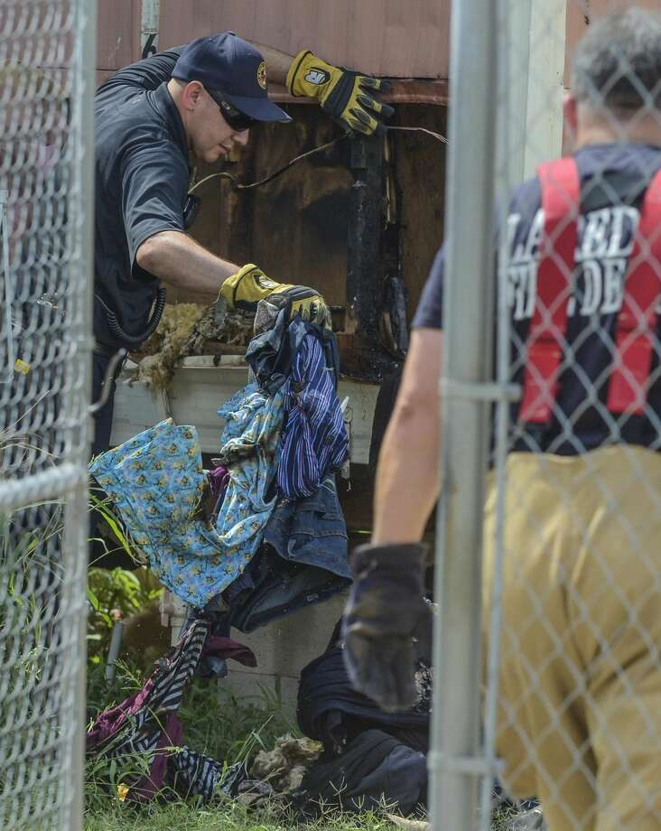 A member of the Laredo Fire Department pulls out damaged clothes from the corner of a mobile home after putting out what authorities think may have been an electrical fire Monday afternoon on the 3200 Block of Guatemozin. No injuries were reported. (Danny Zaragoza/Laredo Morning Times)