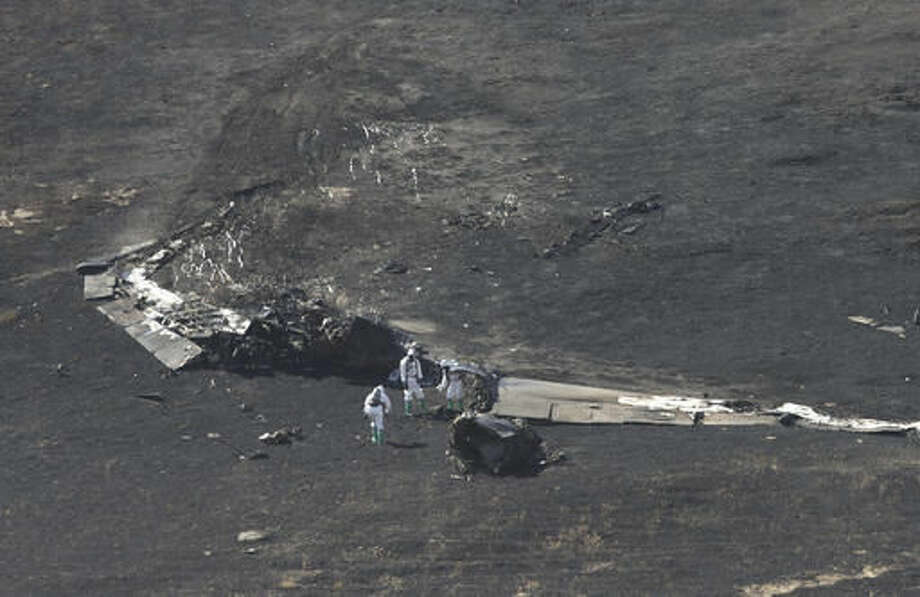 A U.S. Air Force Hazmat team inspects the wreckage of a U.S. Air Force U-2 spy plane that crashed in the Sutter Butte mountains, Tuesday, Sept. 20, 2016, near Yuba City, Calif. One pilot was killed and another injured when they ejected from the plane shortly after taking off from Beale Air Force base on a training mission. (AP Photo/Rich Pedroncelli)