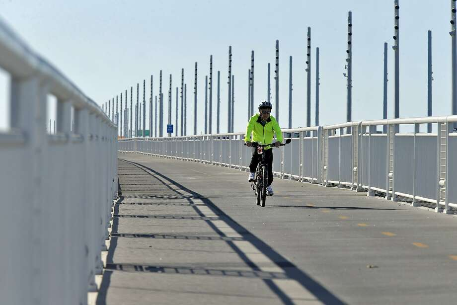 Eugene Lai rides his bicycle down the Pedestrian and Bicycle Path on the Bay Bridge in Oakland, Calif., on Thursday, October 29, 2015. The Bay Bridge bike path from Oakland to Treasure Island has been delayed yet again. Originally scheduled to open along with the new eastern span two years ago, completion had to wait for demolition of part of the old span, which was to be completed by summer. Then it was delayed until late fall/end of the year. Now, it looks like bike riders won't be able to pedal from the East Bay to Treasure Island until sometime next year. Photo: Carlos Avila Gonzalez, The Chronicle