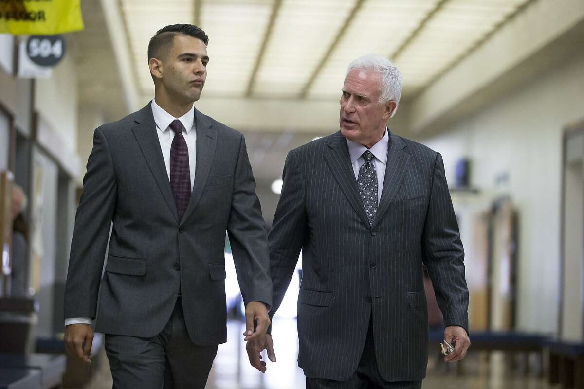 From left: Oakland police officer Giovanni LoVerde and his attorney head to LoVerde's arraignment at the Hayward Hall of Justice, on Friday, Oct. 21, 2016 in Hayward, Calif. LoVerde pleaded not guilty to a sexual misconduct charge.