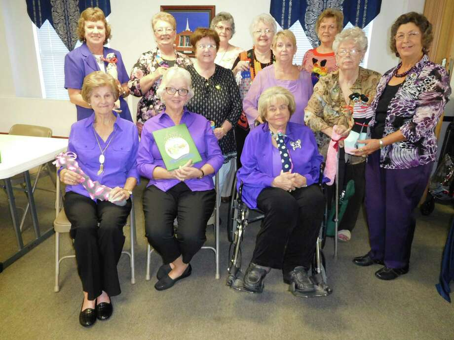 Members of the Woman's Club of Cleveland wore purple to their recent meeting to raise awareness for October as Domestic Violence Awareness Month.  Woman's Club joins with their national organization General Federation of Women's Clubs (GFWC) as well as GFWC Texas to increase education and prevention so vitally needed to stop this horrible crime.  Members are holding care packages to be delivered to local women's shelters – a doubled pair of socks filled with toilet articles and supplies.  Pictured (left to right, back row) are Claire Garrett, Francis Cunningham, Doris Rush, Pat Brooks, Roberta Posey, Linda Lundy, Charlene Capers, Barbara Daniel, Joan Pate; (seated) Claire Barker, President Carol Jordan and Jean McAdams. Photo: Submitted