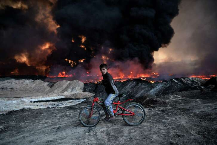 A boy pauses on his bike as he passes an oil field that was set on fire by retreating ISIS fighters ahead of the Mosul offensive Friday in Qayyarah, Iraq. ISIS has forced families to leave their homes for Mosul.